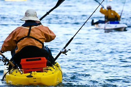 Kayak Fishing - Two men paddling kayaks with fishing gear in the ocean.