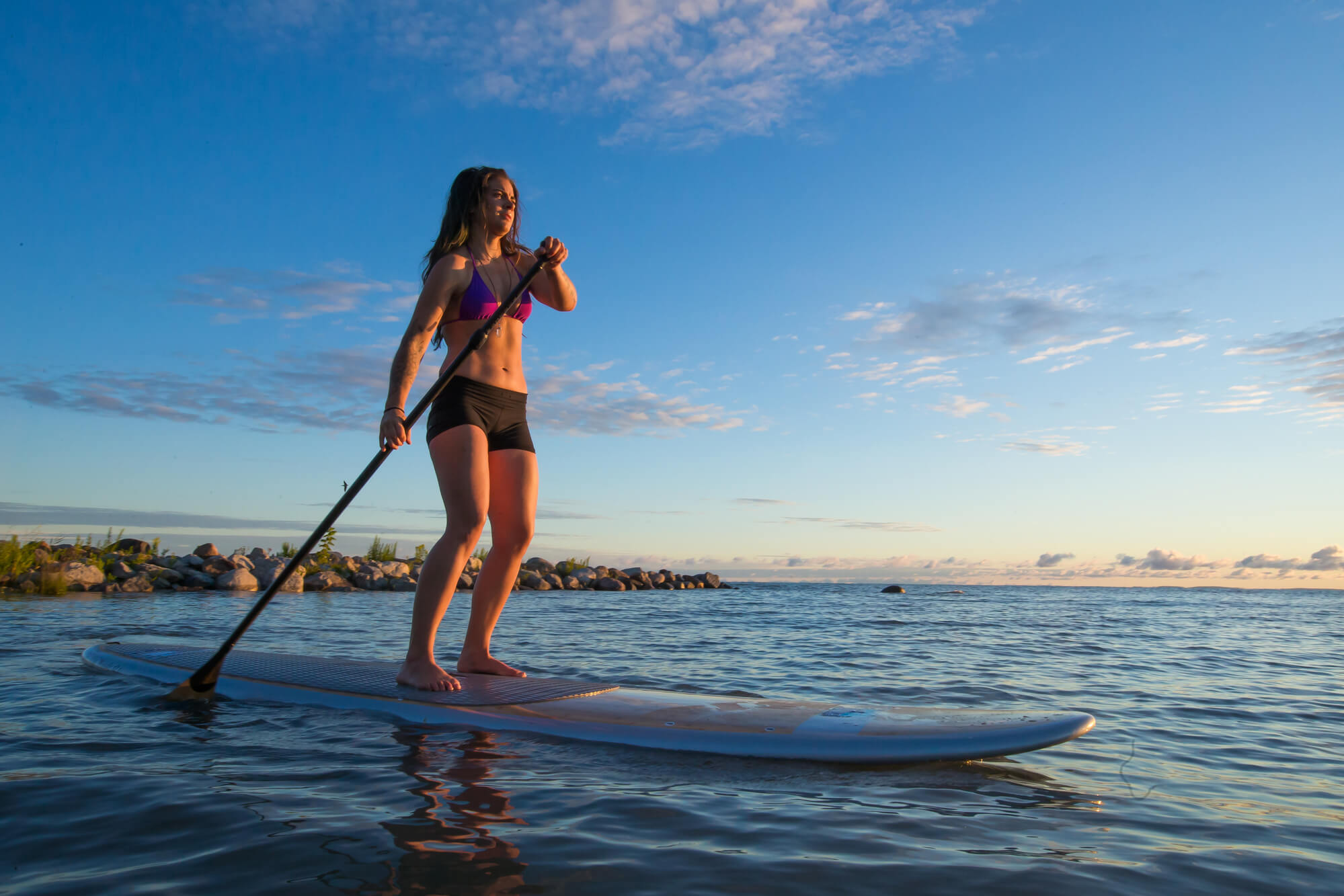 Woman SUP Stand Up Paddling At Sunrise