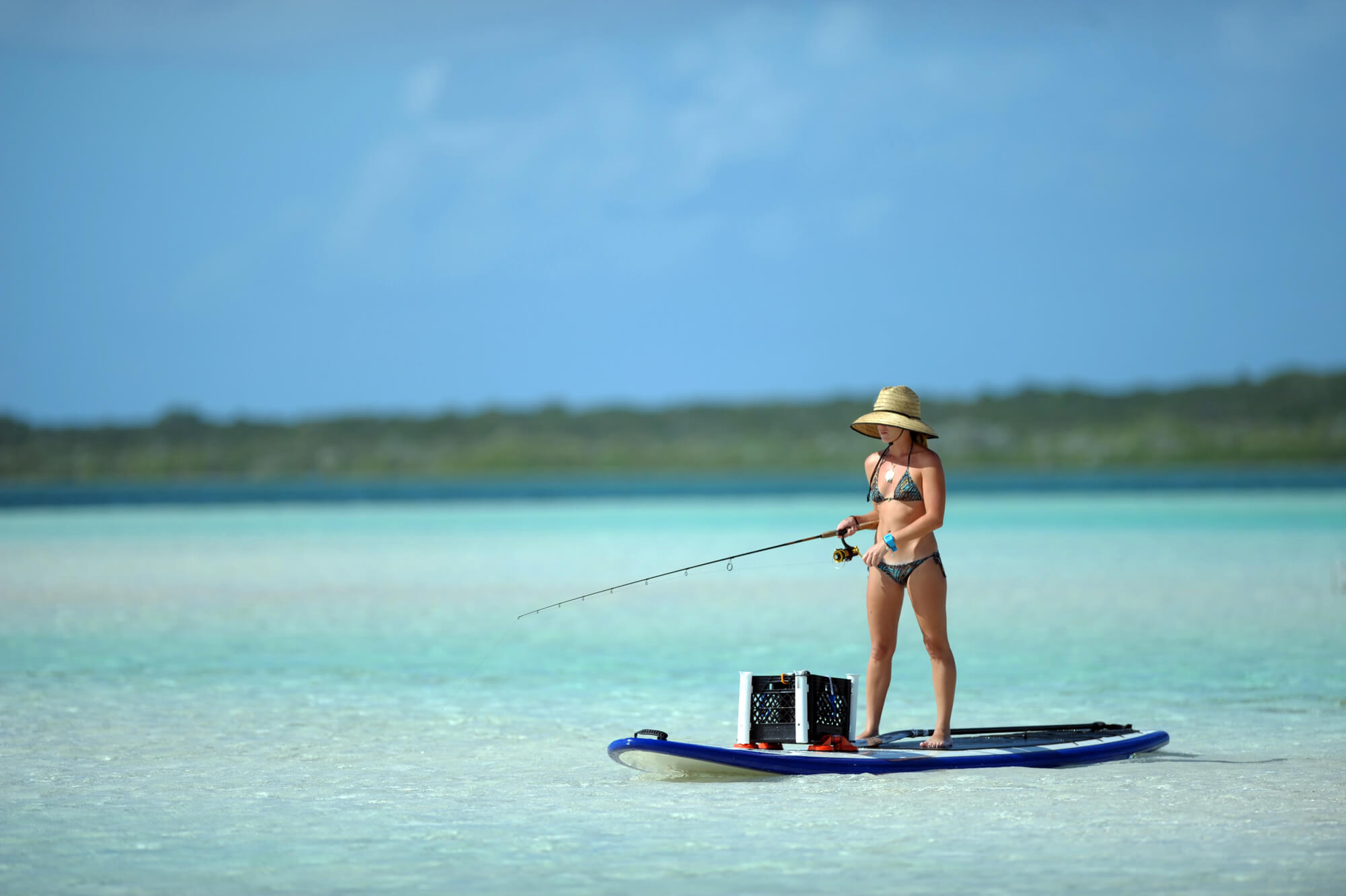 Woman Paddle Board Fishing in the hot sun with hat and sunglasses